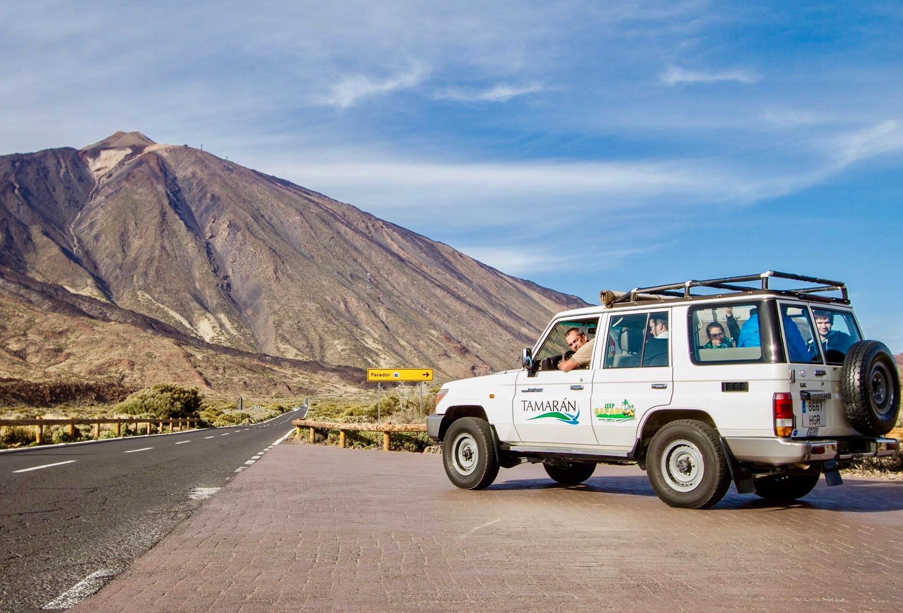 Un conductor de jeep con sus clientes y una vista majestuosa del Teide al fondo.