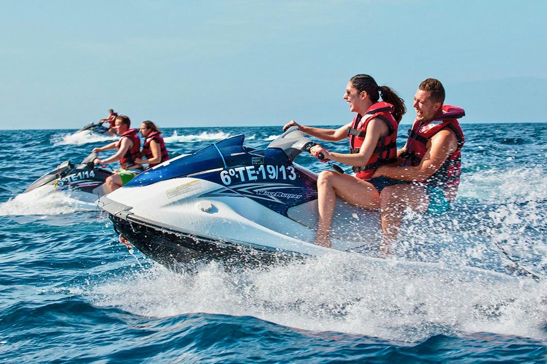 Grupo de amigos en motos acuáticas pasándolo muy bien