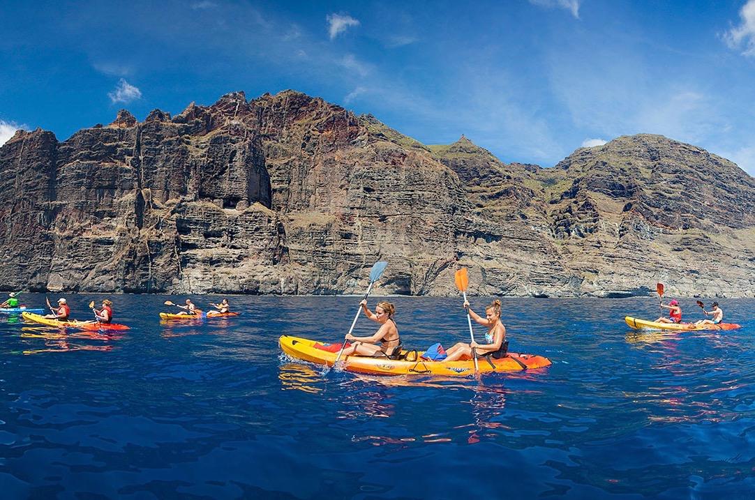 Viajeros en kayak de travesía remando por debajo del inmenso acantilado vertical de Los Gigantes