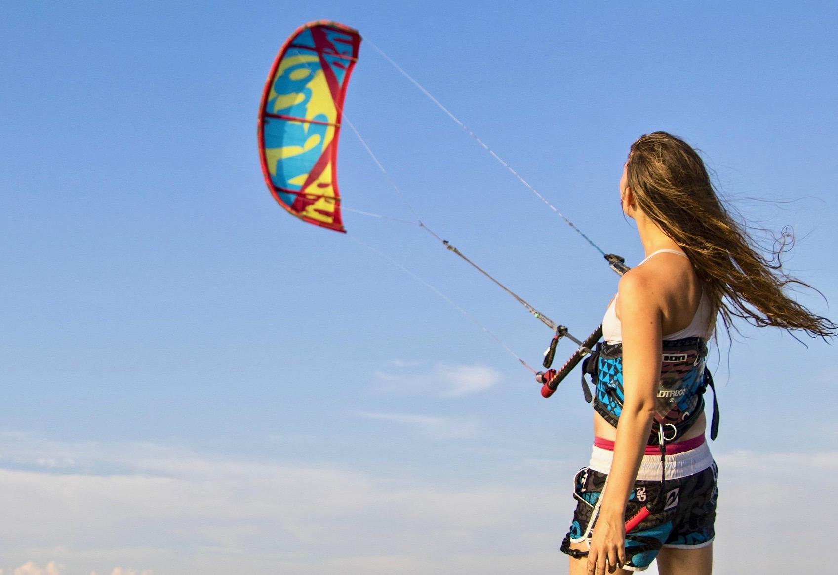 Una niña practicando su habilidad de control de kite antes de practicar kitesurf en el mar.