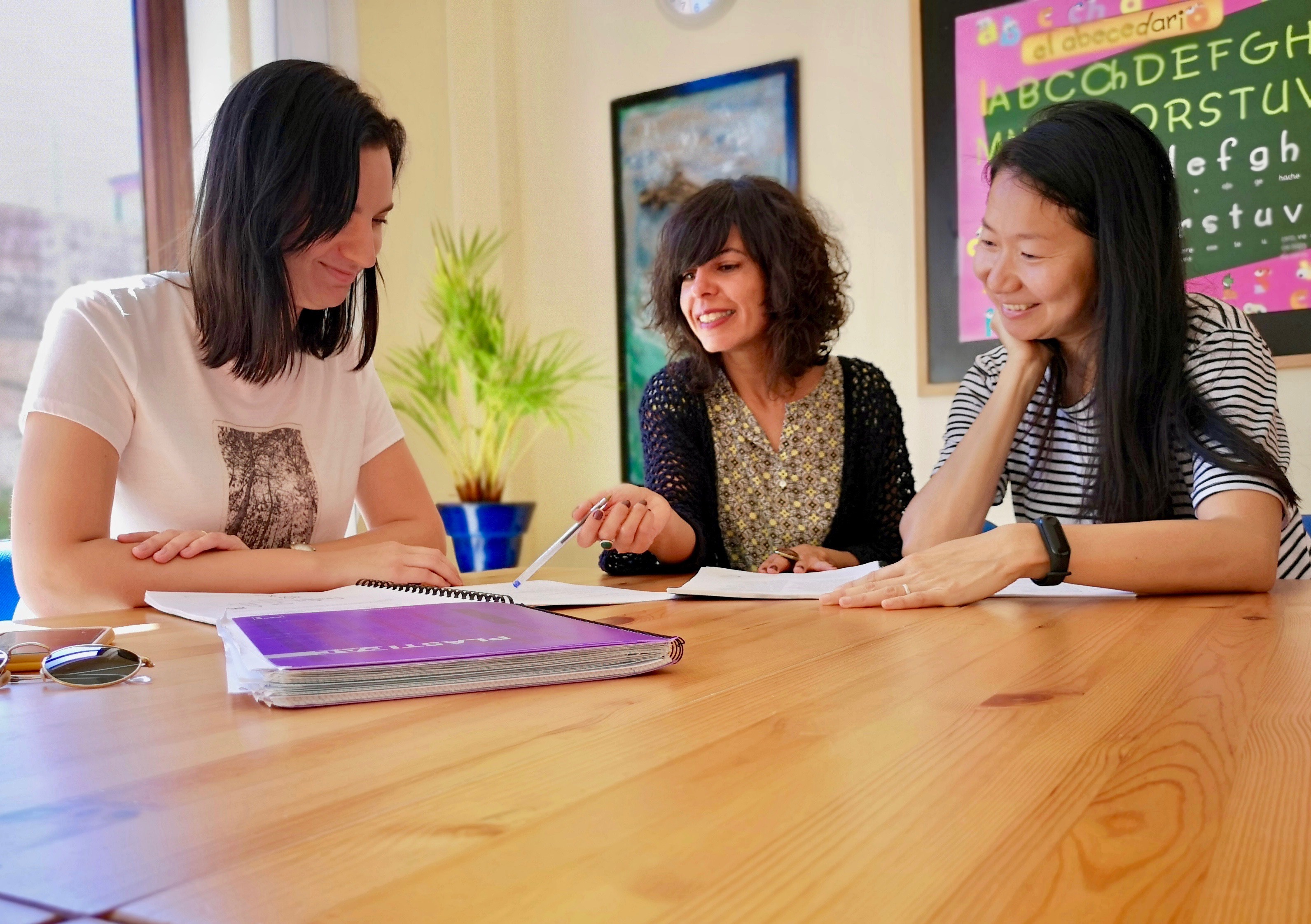 Una profesora de idiomas explicando gramática a sus dos alumnos en un aula luminoso.
