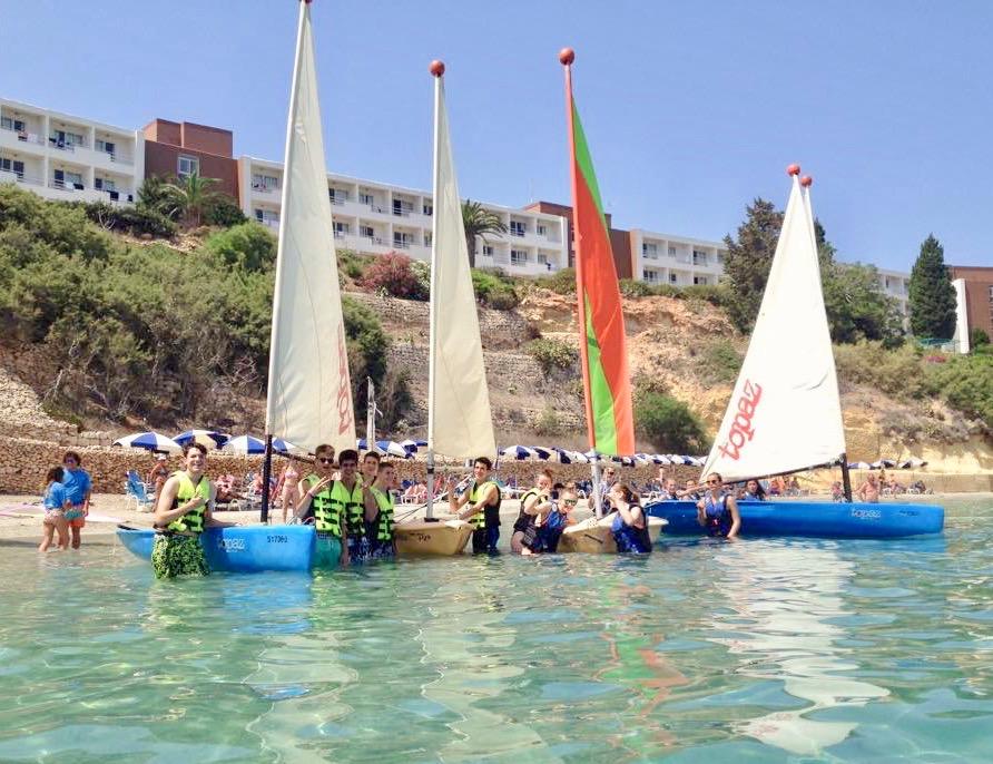 Jóvenes con sus mini veleros en la playa listos para partir