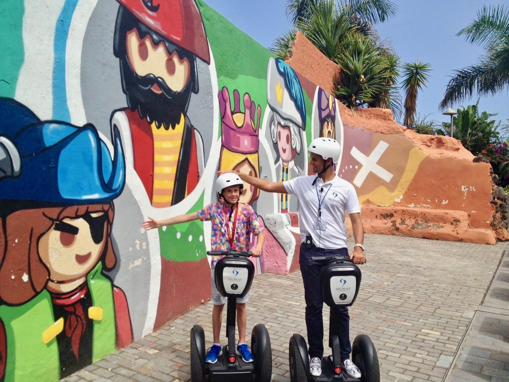 Un guía turístico en Segway con una niña pequeña que se detiene en un colorido mural de dibujos animados en el Puerto de la Cruz.