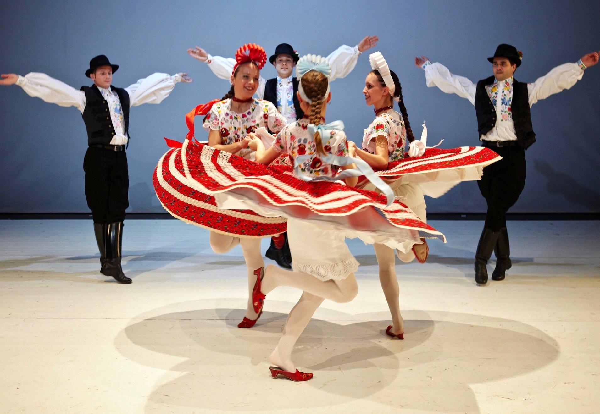 Bailarines folclóricos húngaros vestidos con trajes de colores que bailan una danza tradicional.