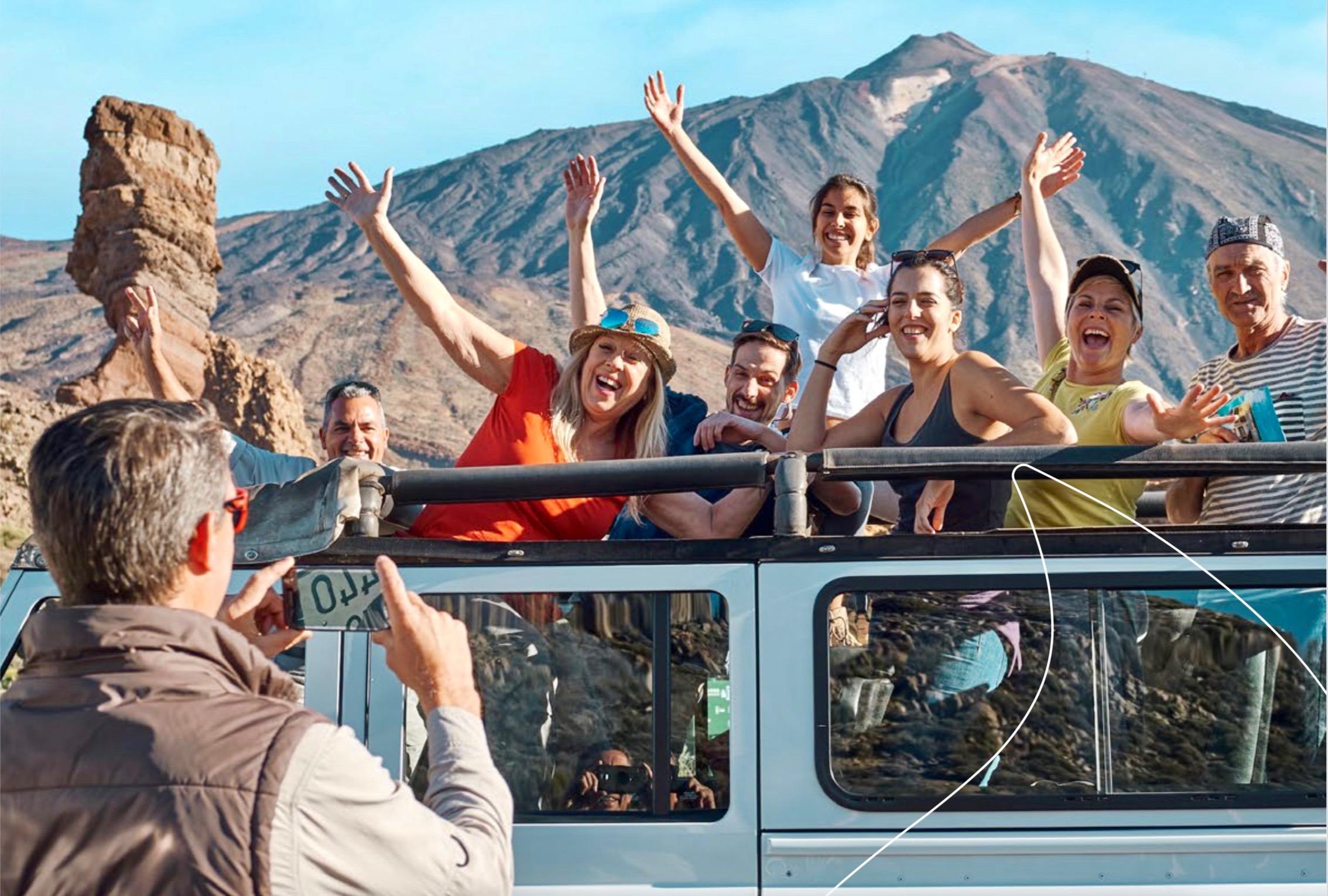 Un grupo de viajeros en una excursión turística felizmente posando para la foto frente al volcán Teide