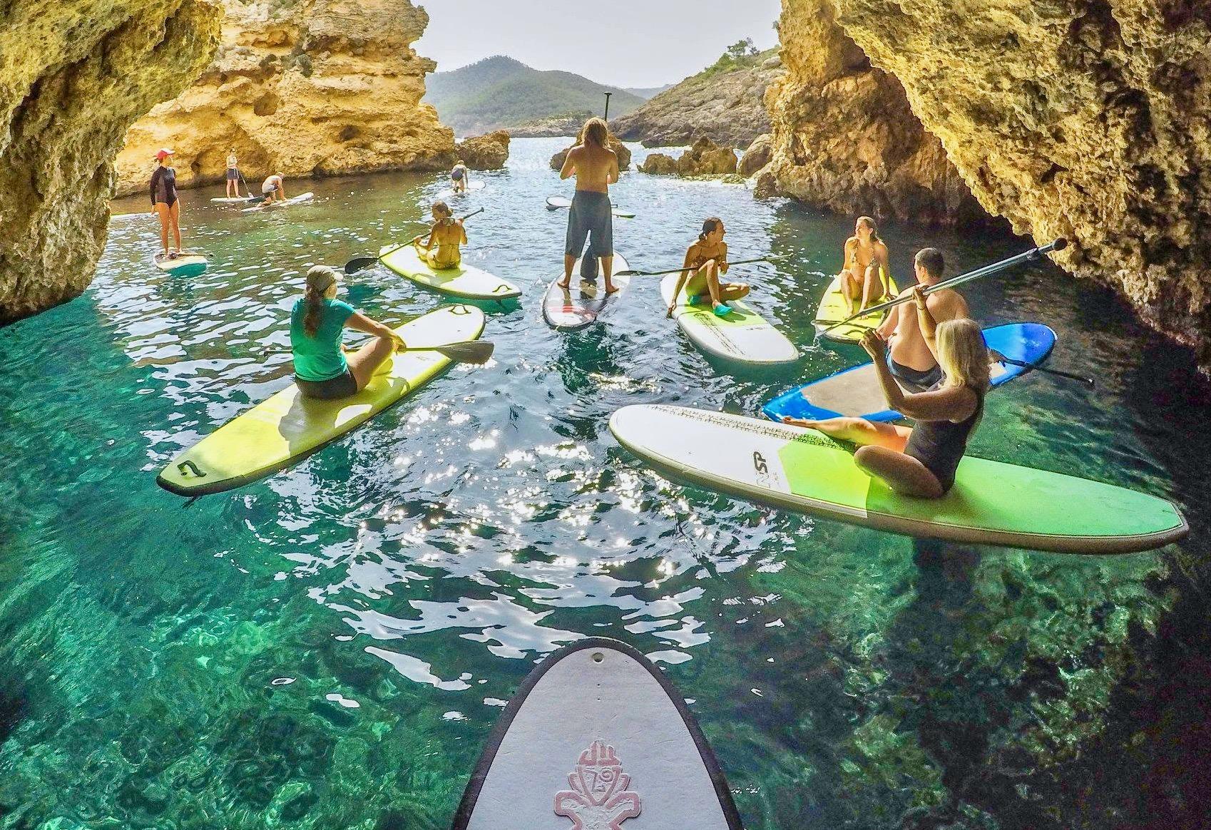 Un grupo con tablas SUP haciendo una pausa dentro de una hermosa cueva con agua cristalina debajo de ellos.