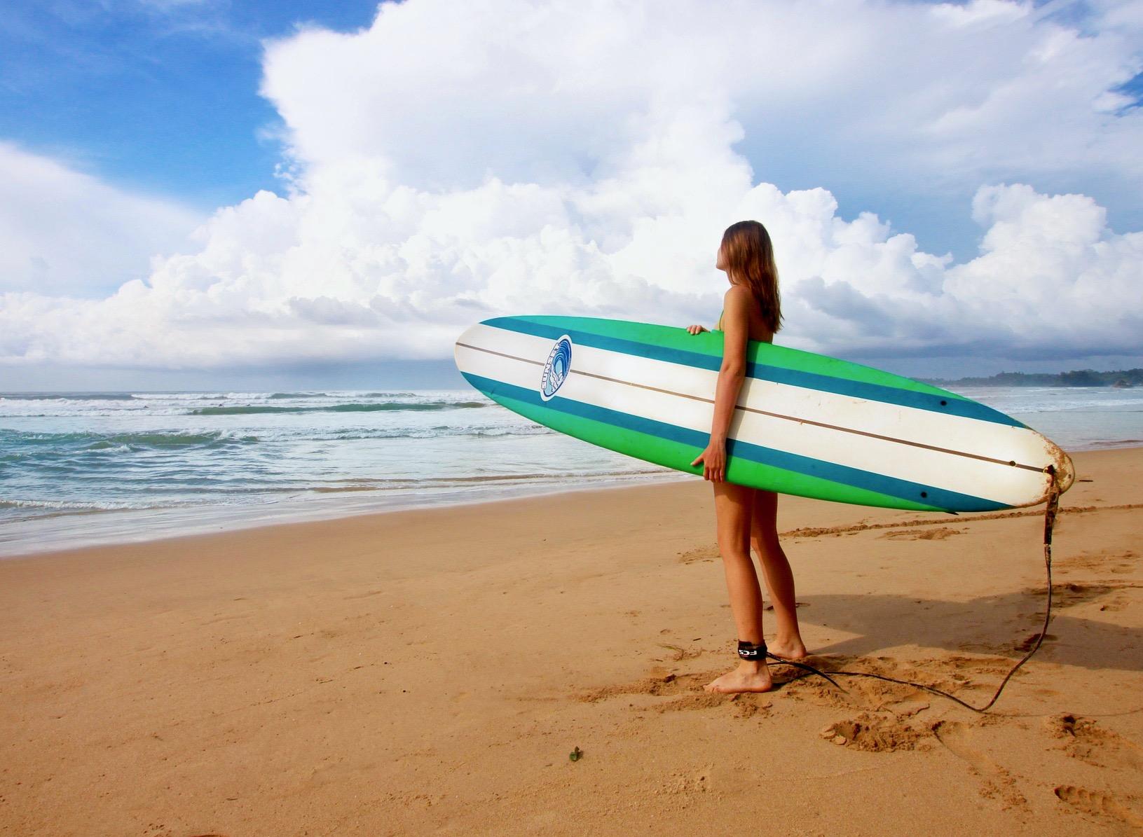 Una chica con una tabla de surf mirando al mar buscando olas antes de meterse en el agua.