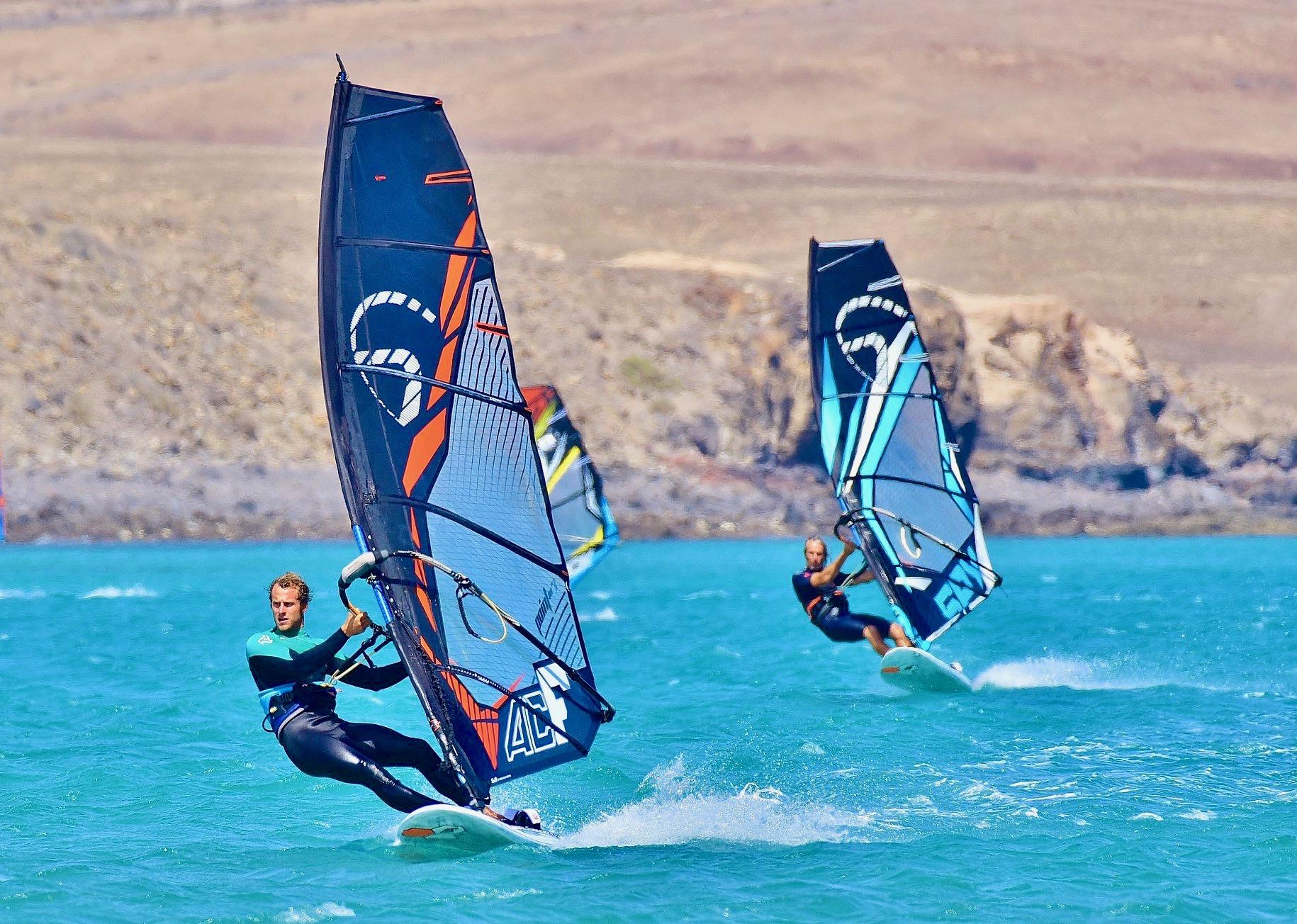 Dos windsurfistas practicando sus habilidades de windsurf en aguas turquesas