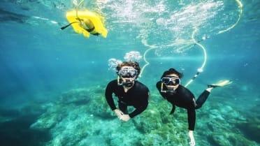 Couple enjoying underwater scuba snorkel in Lobos island