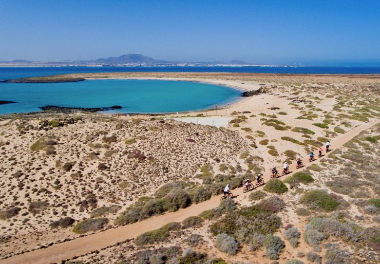 Cycling in Lobos island with white sand beach and turquoise waters